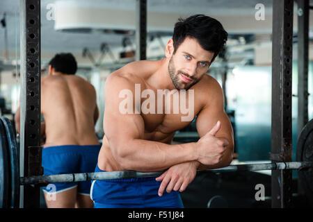Porträt eines schönen muskulösen Mannes zeigt Daumen sich im Fitness-Studio - Stockfoto