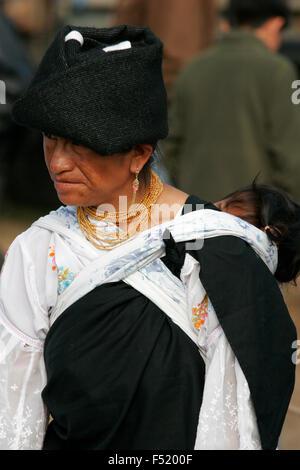 Indigene Frau tragen traditionelle Kleidung mit Baby auf dem Rücken in Otavalo Markt, Ecuador, Südamerika bekommen - Stockfoto