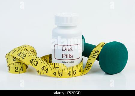 Container von Diät-Pillen mit gelben Maßband und Gewicht. - Stockfoto