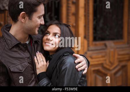 Porträt von einem glücklichen paar umarmt im Freien mit alten Holztür auf Hintergrund - Stockfoto