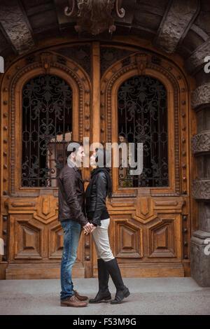 Voller Länge Porträt eines jungen Paares Flirten im Freien mit alten Holztür auf Hintergrund - Stockfoto