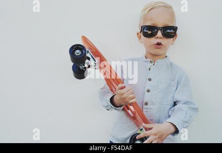 Entzückende Hipster kleiner Junge mit einem Skateboard tragen Sonnenbrillen entlehnt seine Mama oder Papa sich gegen - Stockfoto