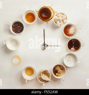 Kaffee Clock.Clock gemacht von einem Dutzend Tassen Kaffee (mit Kaffeebohnen, Milch und Spritzer). Es ist immer Kaffeezeit! Stockfoto