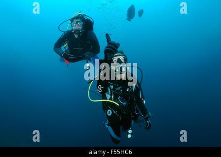 Junges Paar Taucher schwimmt im Wasser, Frau, die etwas auf die Finger, Indischer Ozean, Malediven - Stockfoto