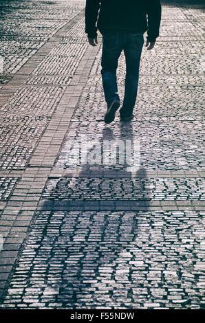 Geheimnisvollen männlichen Figur, die zu Fuß auf gepflasterten Straße - Stockfoto