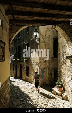Alte Frau in einer sonnigen alte gepflasterte Gasse der Stadt Rovinj, Istrien, Kroatien - Stockfoto
