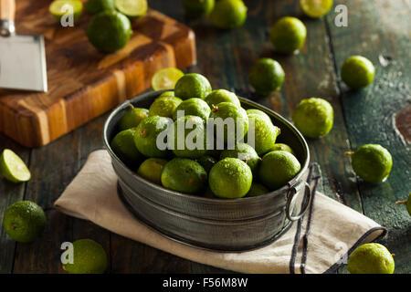 Rohe grüne Bio Key Limes in eine Schüssel geben