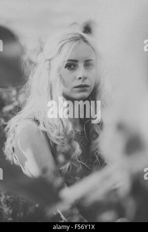 Schöne junge Frau in einem Sonnenblumenfeld an goldene Stunde Stockfoto