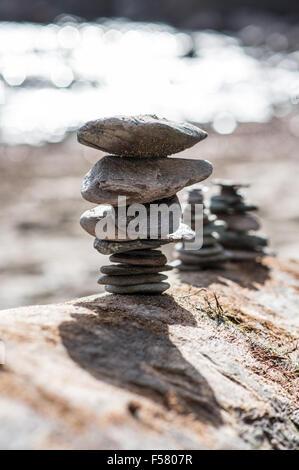 Dünne Kieselsteine sorgfältig ausgewogen auf driftete Log zeigt Struktur und Tiefe der Farbe im Stil des Künstlers - Stockfoto