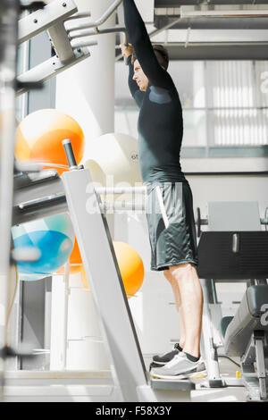 Hübscher Jüngling, ein Fitnessraum und eine gesunde Lebensweise - Stockfoto