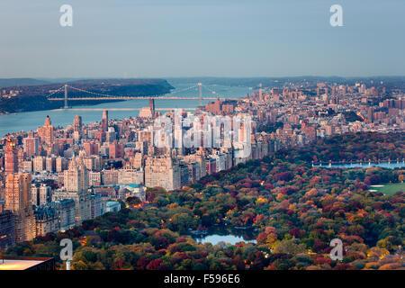 Sonnenuntergang Luftaufnahme der Upper West Side von Manhattan und den Central Park im Herbst mit George Washington Bridge und Hudson River. NEW YORK CITY