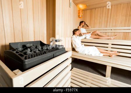 Saunaofen in eine gemütliche Sauna und Mädchen entspannen im Hintergrund - Stockfoto