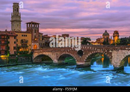 Ponte Pietra Bridge in der Dämmerung über der Etsch in Verona, Italien - Stockfoto