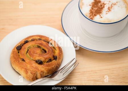 Ein frisches Pain au Rosinen und ein Cappuccino-Frühstück - Stockfoto