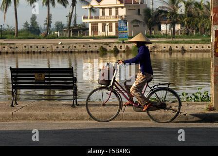 Radfahrer-Frau auf der Promenade am Thu Bon Fluss in Hoi An Vietnam. Typischen Vietnamesischen Frau mit Hut. - Stockfoto
