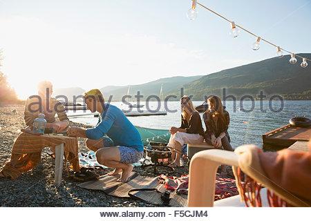 Junge Freunde hängen am sonnigen Seeufer - Stockfoto
