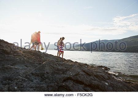 Junge Freunde, die zu Fuß auf den Felsen am sonnigen See - Stockfoto