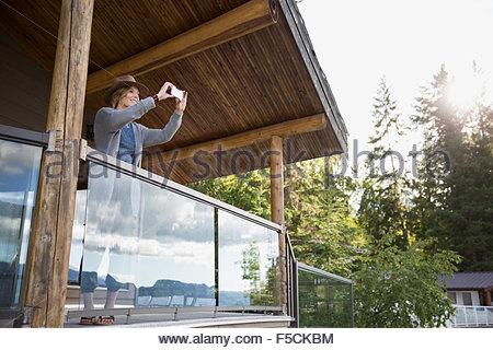Junge Frau mit Kamera-Handy auf Kabine Balkon - Stockfoto