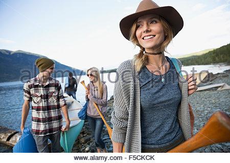 Lächelnde junge Freunde mit Kanu am Seeufer - Stockfoto