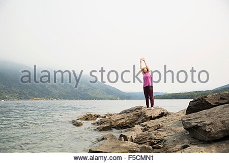Reife Frau praktizieren Yoga auf Felsen am See - Stockfoto