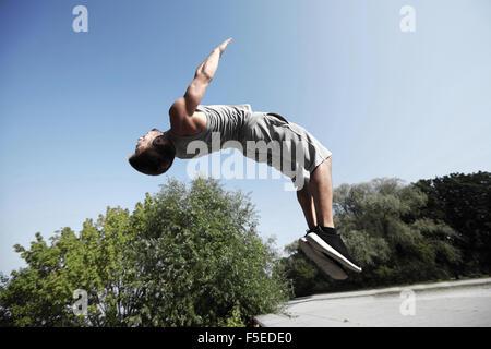 sportliche junge Mann springt im Sommerpark - Stockfoto
