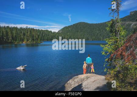 Mann mit zwei Kindern, die auf einem Felsen See - Stockfoto