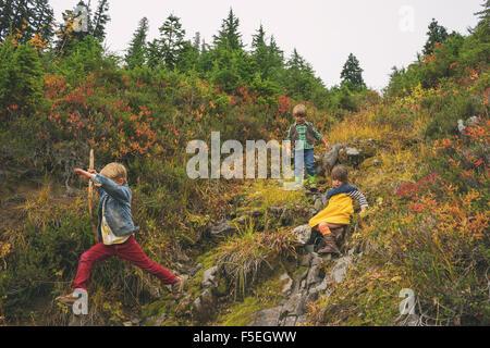 Drei Kinder, die einen Berg hinunter - Stockfoto