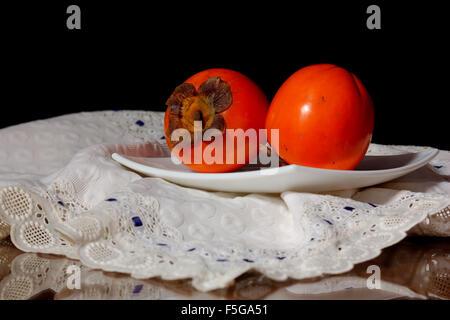 Ein paar Kaki auf einem Teller, mit dunklem Hintergrund und Tischdecke. - Stockfoto