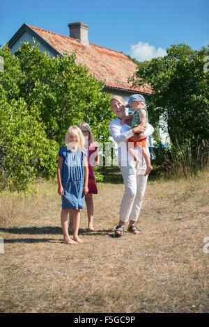Schweden, Gotland, Faro, Mutter mit Töchtern (8-9, 10-11) und Sohn (2-3) im Hinterhof - Stockfoto