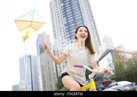 Junge Frau zieht einen Drachen hinter ihr Fahrrad - Stockfoto