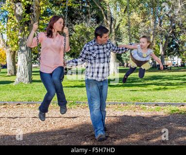 Vater, Mutter und niedliche kleine Tochter spielen auf Park schwingt - Stockfoto