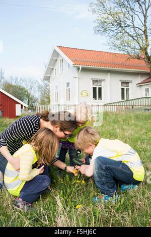 Schweden, Vastergotland, Olofstorp, Bergum, Frau, die Betreuung der Kinder (2-3, 4-5, 6-7) im freien - Stockfoto
