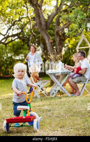 Familie mit drei Kindern (12-17 Monate, 2-3) in Hinterhof, Havdhem, Gotland, Schweden - Stockfoto