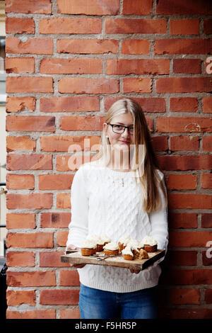 Schweden, Uppland, Mädchen (14-15) mit Cupcakes gegen Mauer - Stockfoto