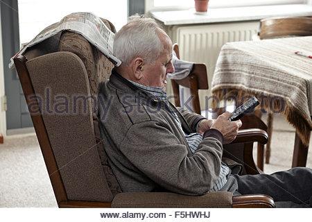 älterer Mann im Sessel mit Fernbedienung Fernsehen - Stockfoto