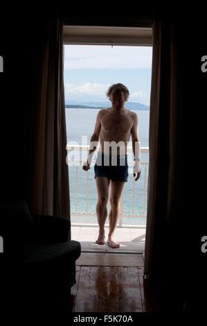 Mann in Badehose im Fenster - Stockfoto