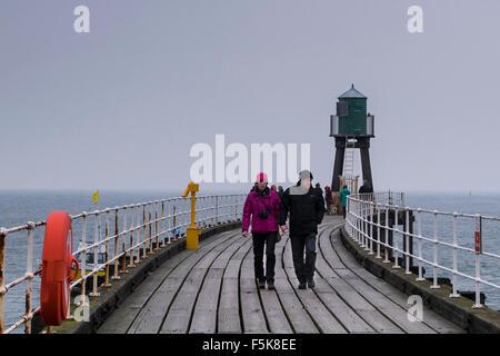 Menschen in warme Kleidung, zu Fuß auf Whitbys West Pier Erweiterung, England, UK - graue Holzbretter, Meer und - Stockfoto