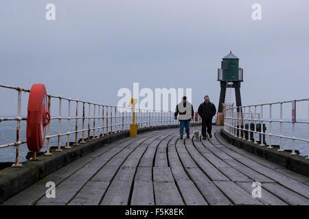 Paare, die einen Hund auf Whitbys West Pier, reflektieren England, UK - Grautöne Holzbretter, des Meeres und des - Stockfoto