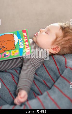 Schweden, Vastra Gotaland, Göteborg, Mädchen (12-17 Monate) schläft mit Buch an des Vaters Brust - Stockfoto