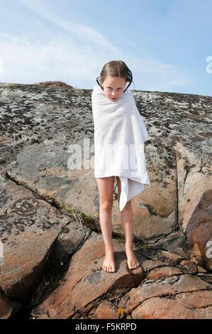 Schweden, Halland, Onsala, Mädchen (6-7) gewickelt Handtuch, auf Felsen - Stockfoto
