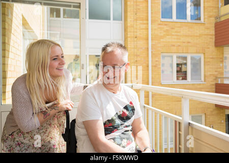 Schweden, Ostergotland, Mjolby, Mann im Rollstuhl mit persönlicher Assistent auf Balkon - Stockfoto