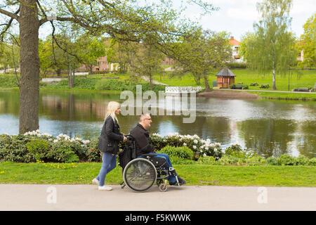 Schweden, Ostergotland, Mjolby, Mann im Rollstuhl mit persönlicher Assistent im park - Stockfoto