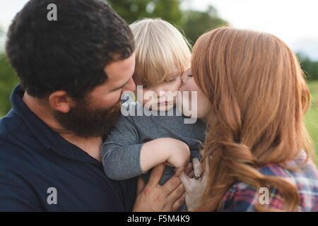 Mutter und Vater Holding jungen Sohn, im freien - Stockfoto