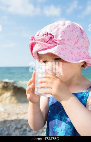 Weiblichen Kleinkind Trinkwasser am Strand - Stockfoto