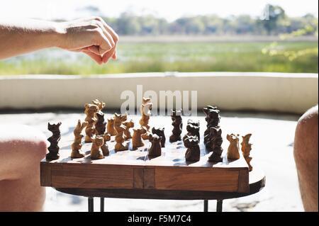 Beschnitten, Schuss von Frau und Mann spielt Schach in der Safari Lodge, Kafue Nationalpark, Sambia