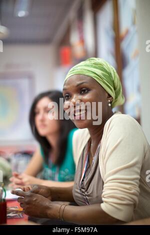 Mitte der erwachsenen Frau, sitzt am Schreibtisch Lächeln - Stockfoto