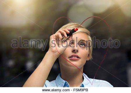 Junge Frau Lippenstift Herzform auf Fenster zeichnen - Stockfoto
