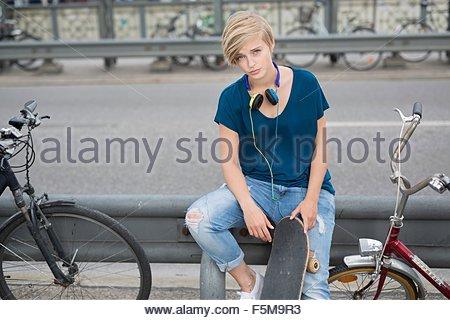 Porträt der jungen Frau mit Skateboard sitzt auf Barriere - Stockfoto