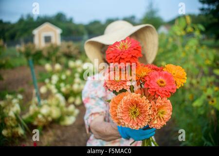 Ältere Frau mit Blumen vor Gesicht auf Bauernhof Stockfoto
