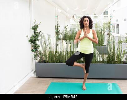 Reife Frau tun Yoga-Baum-pose - Stockfoto